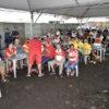 Pessoas com uniformes de escolas de samba acompanham apuração de voltos sob tenta enquanto chove