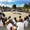 Roda de capoeira, com crianças de uniforme escolar e pessoas com roupa de capoeira