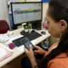 Foto de costas de mulher sentada, segurando celular, com mesa e computador de trabalho ao fundo
