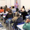 professor e sala de aula repleta de alunos sentados