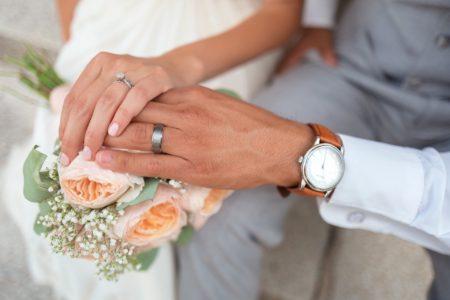 Mãos dos noivos com alianças sobre buquê de flores