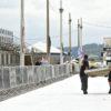 Avenida com chão pintado de branco, com homens carregando material, com caminhão à frente e arquibancada dos lados