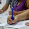 Mão de aluna, preenchendo a ficha de inscrição com caneta azul