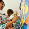 Aluna do Fundo Social pintando tela colorida. Ao fundo outra aluna.