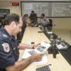 Homem com farda de guarda lê mapa impresso em folha, com outros policiais ao fundo e telão com projeção de câmeras ao fundo