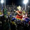 Local de desfile das escolas de samba, com público assistindo e carros alegóricos desfilando, com fantasias