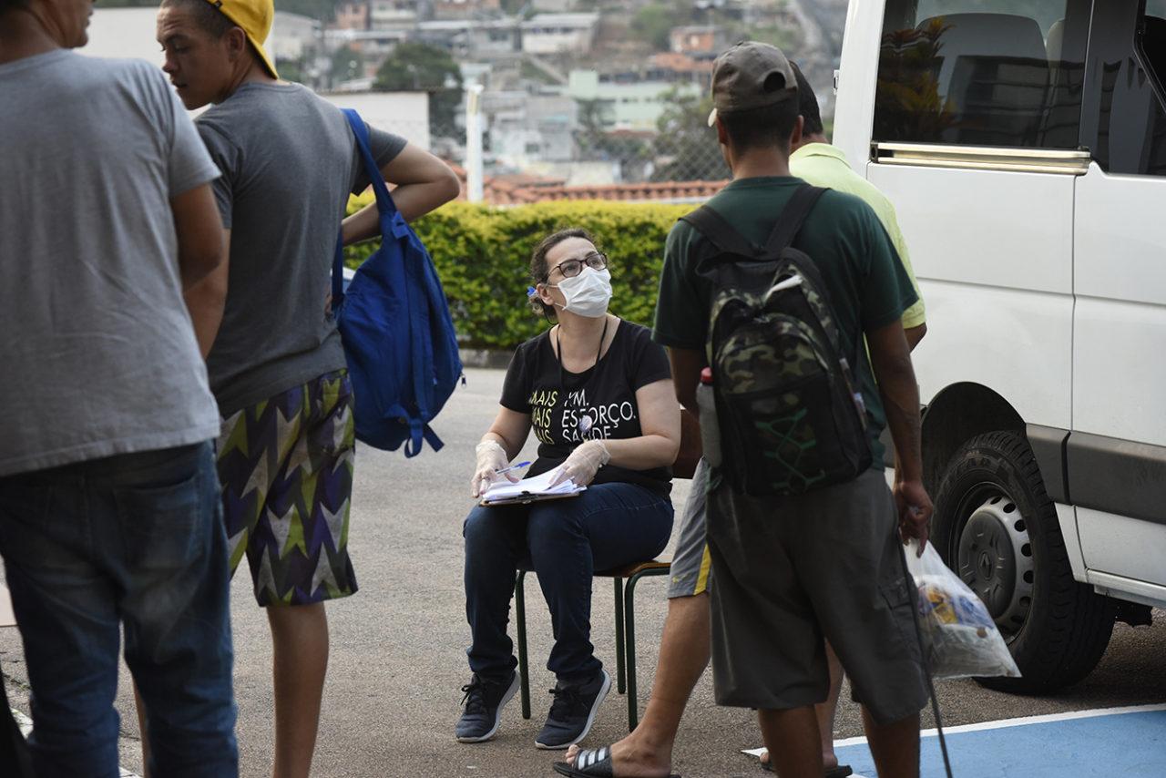 Mulher sentada, usando luvas e máscaras, tomando anotações em prancheta, enquanto conversa com pessoas para serem atendidas