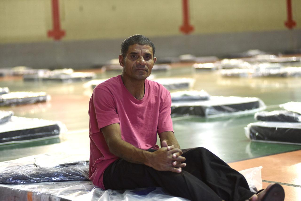 Homem sentado sobnre colchão, com diversos outros colchões ao fundo, sobre chão de ginásio coberto