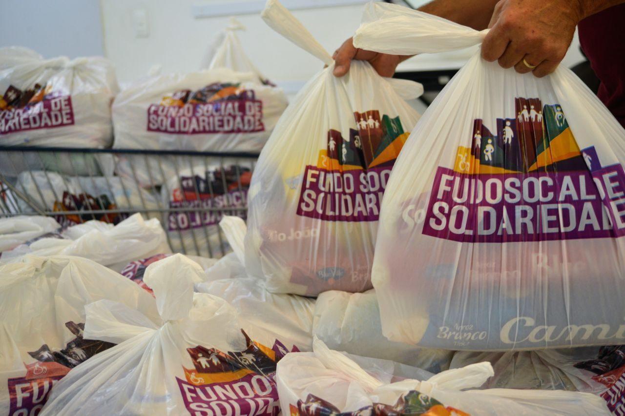 Mãos seguram cestas básicas em sacolas com logomarca do Fundo Social