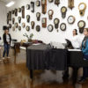Pessoas em pé, conversando ao redor de piano, com parede com relógios ao fundo