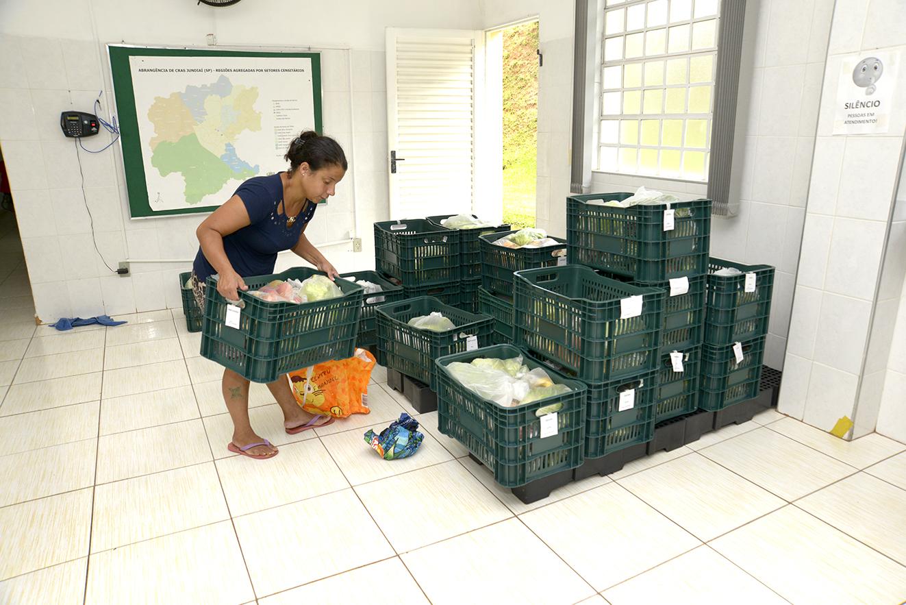 Mulher manuseia caixa de plástico com sacolas dentro