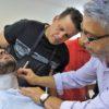 Professor ensinando dois alunos no curso de barbearia em atividade prática