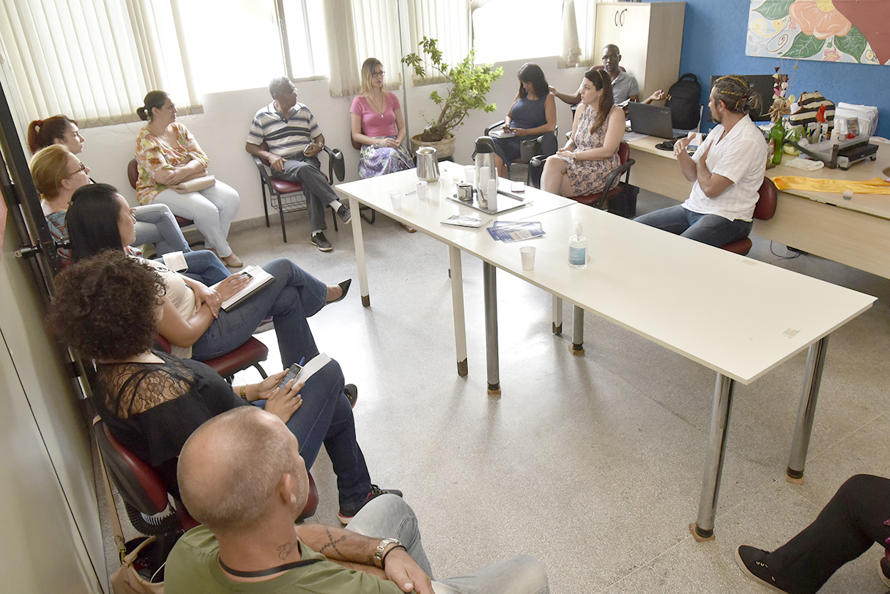 Sala de reunião, com diversas pessoas conversando sentadas, dispostas em círculo, com meso no centro