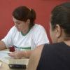 Uma mulher atende a outra, sentadas defronte a uma mesa, manuseando docmentos