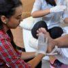 alunas de curso de cuidador de idosos em atividade prática com idoso