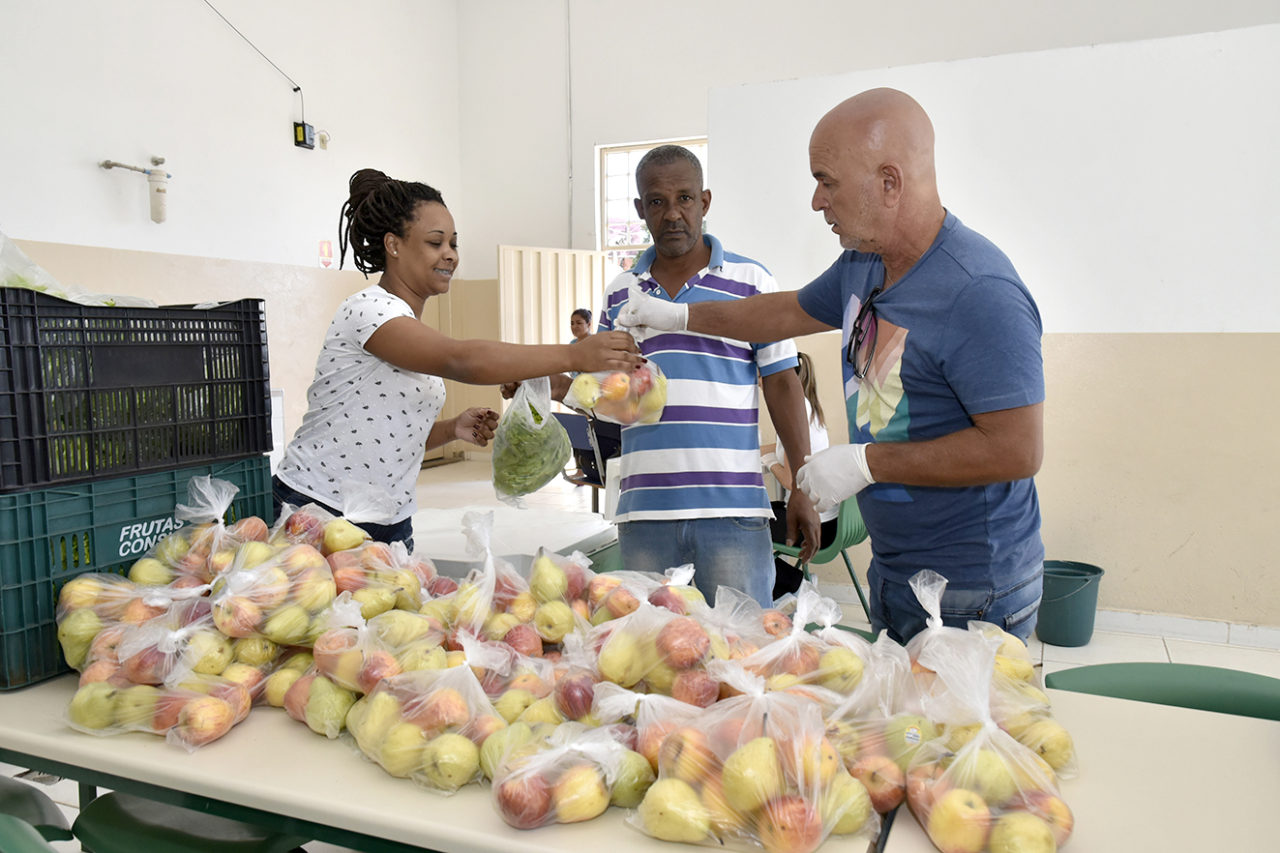 Mulher recebe sacola com pé de alface, com mesa com sacolas com peras e maçãs