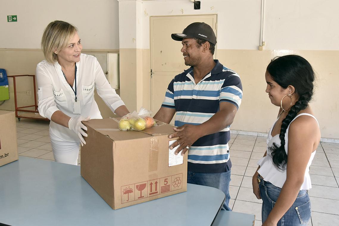 Mulher entrega a casal caixa com sacola com maçãs em cima
