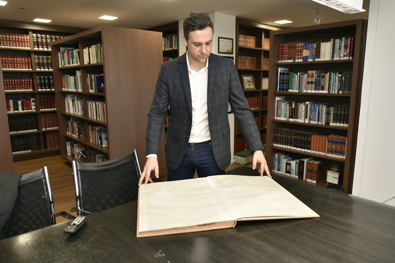 Foto dentro de biblioteca com estantes de livros, homem em pé folheia encadernação em tamanho grande, apoiado sobre mesa