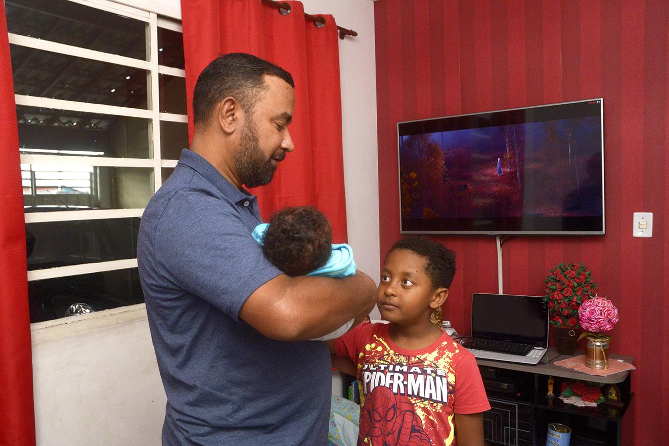 Homem em pé segurando bebê, com criança em pé, brincando com o bebê, e paredes ao fundo com janela e cortina e televisão em que se vê desenho animado