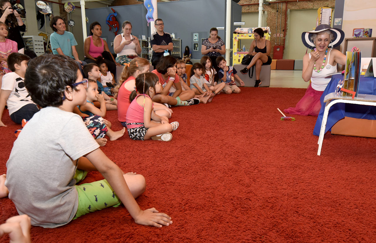 Crianças sentadas sobre tapete, assistindo a uma apresentação de contação de histórias