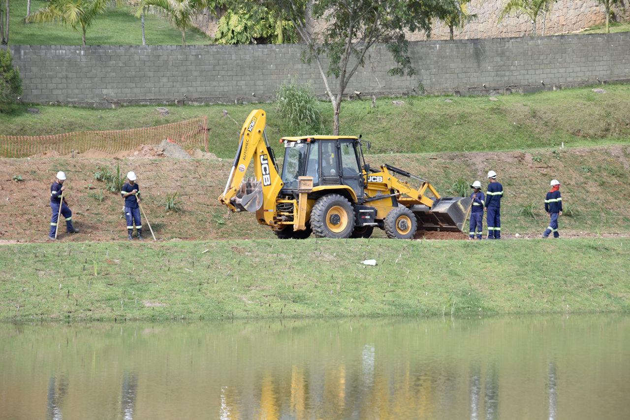 Homens trabalham no gramado do entorno de uma das lagoas