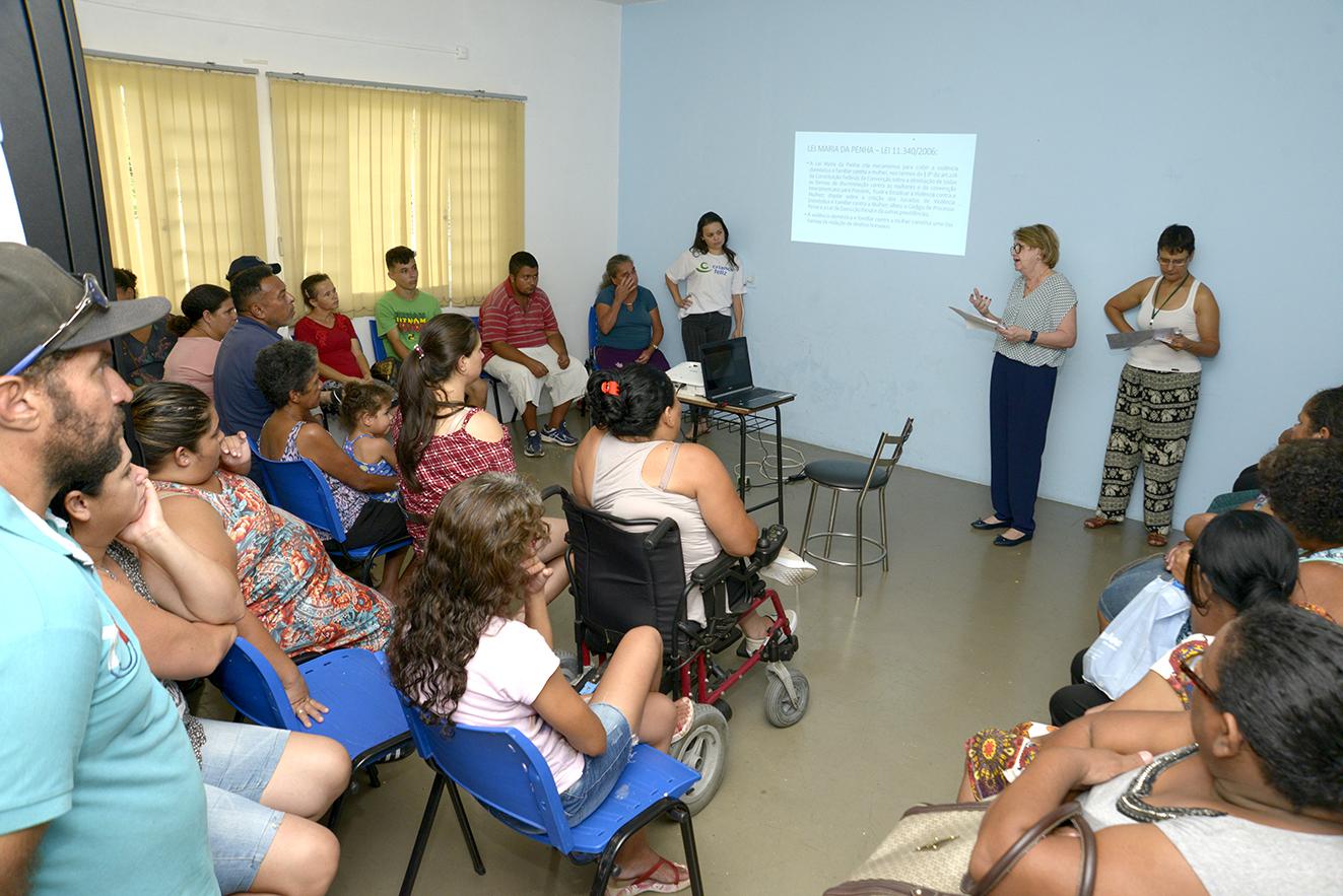 Sala de aula, com pessoas sentadas, e palestrante em pé à frente, com projeção feita sobre a parede