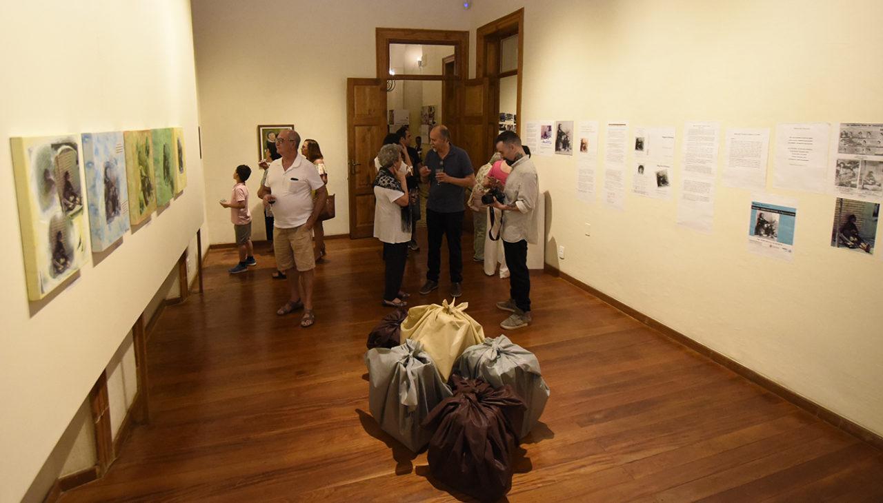 Sala de exposição, com quadros nas paredes, objetos como sacolas e pacotes no centro, e pessoas conferindo