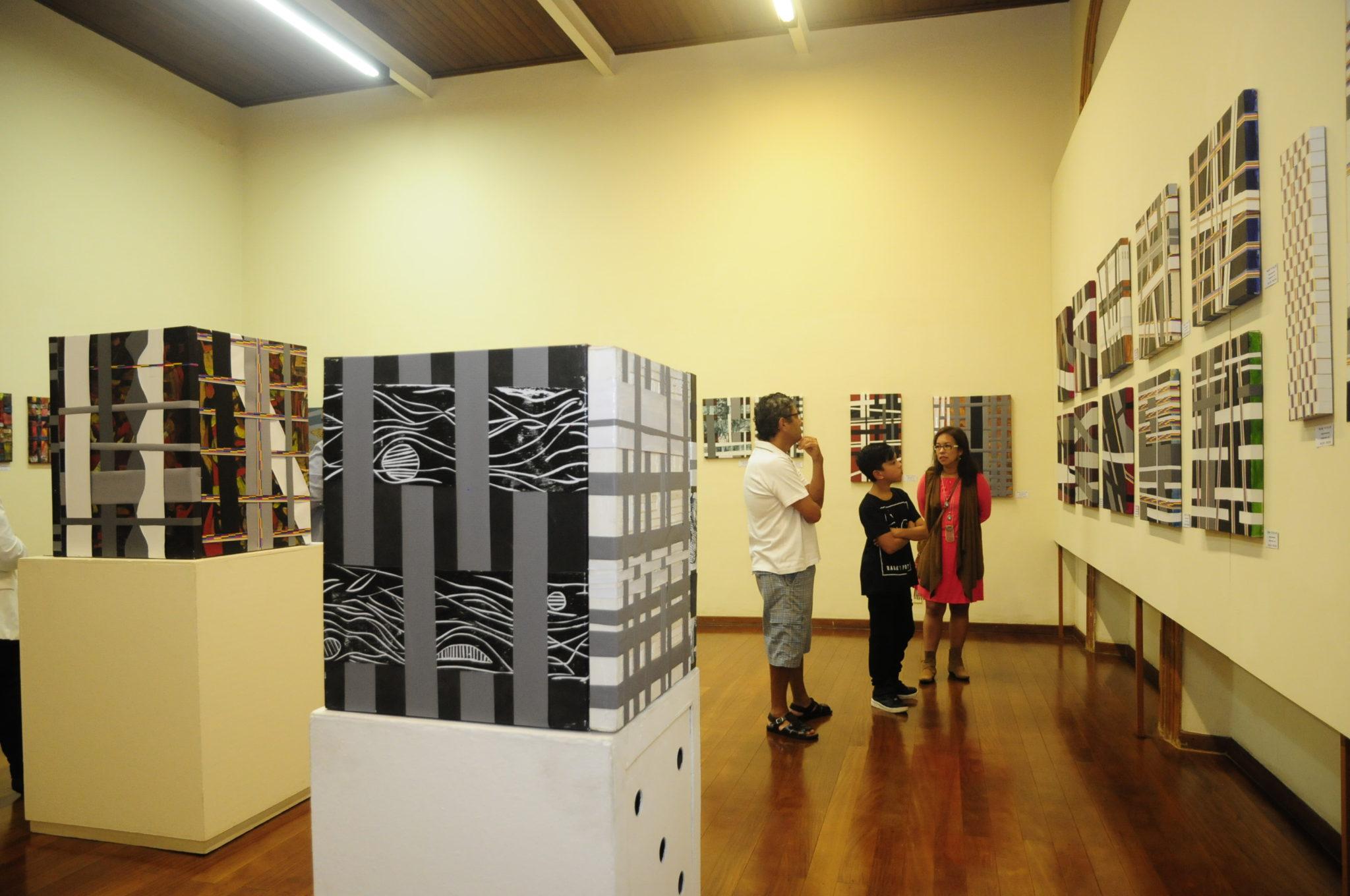 Sala de exposições, com homem, mulher e criança olhando para quadros abstratos e conversando