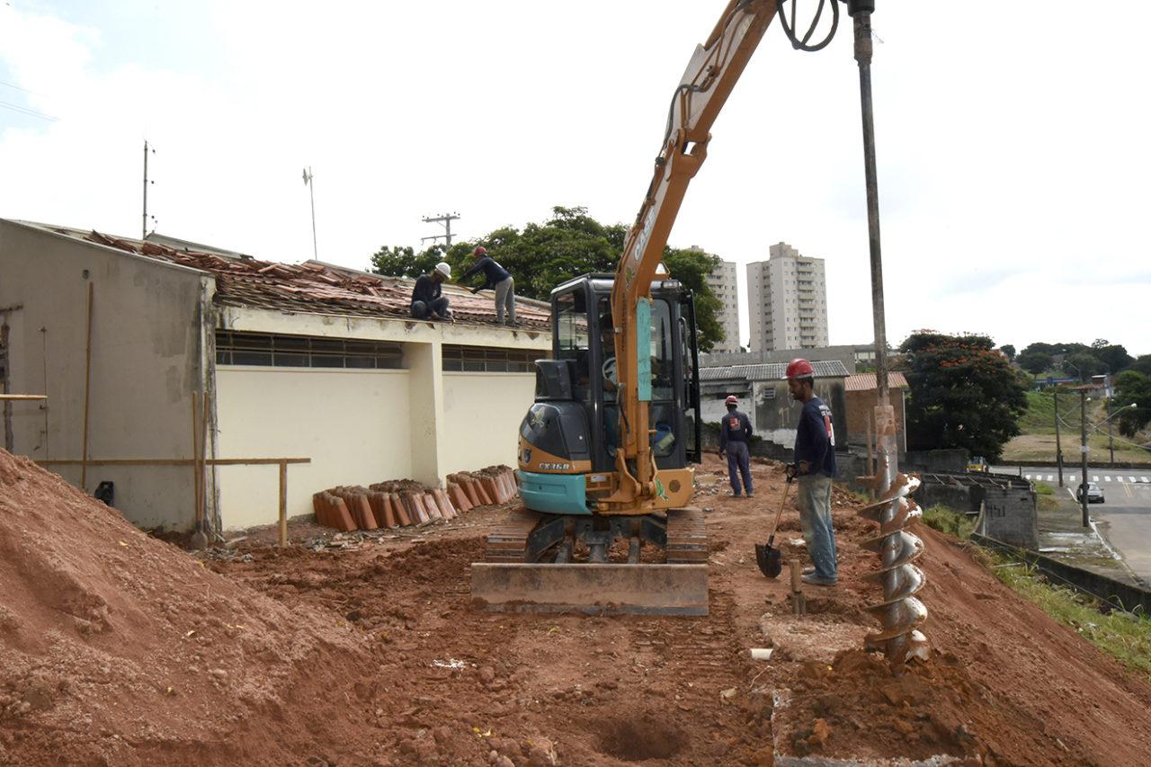 Perfuratriz de solo em operação, com operários em canteiro de obras e sobre telhado