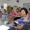 Mulheres sentadas em círculo, conversando, com uma mulher posando sorridente