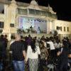 Foto noturna de coreto com banda se apresentando e público assistindo