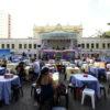 Praça com coreto ao fundo e mesas, com pessoas sentadas comendo