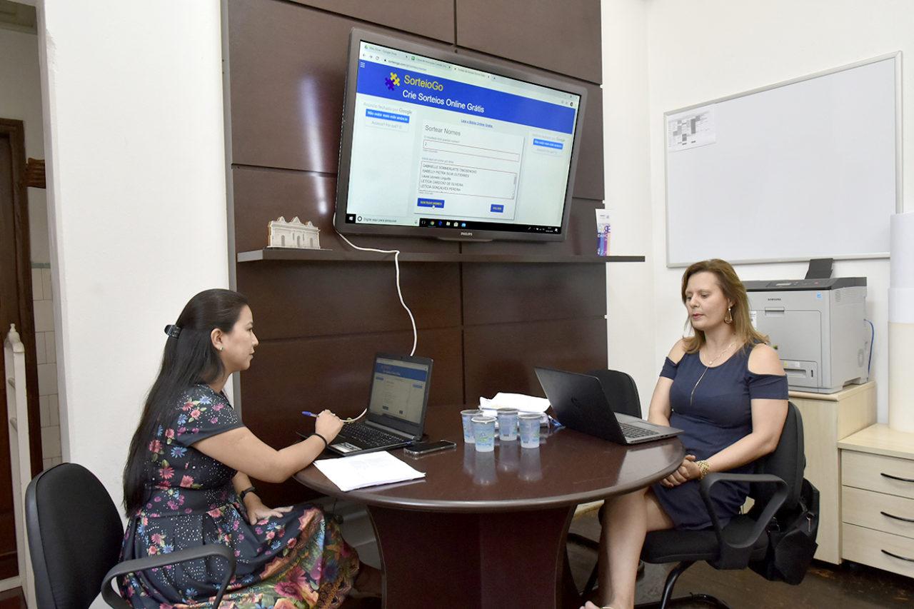 Duas mulheres sentadas no entorno de uma mesa com computadores, e tele com imagens afixada na parede