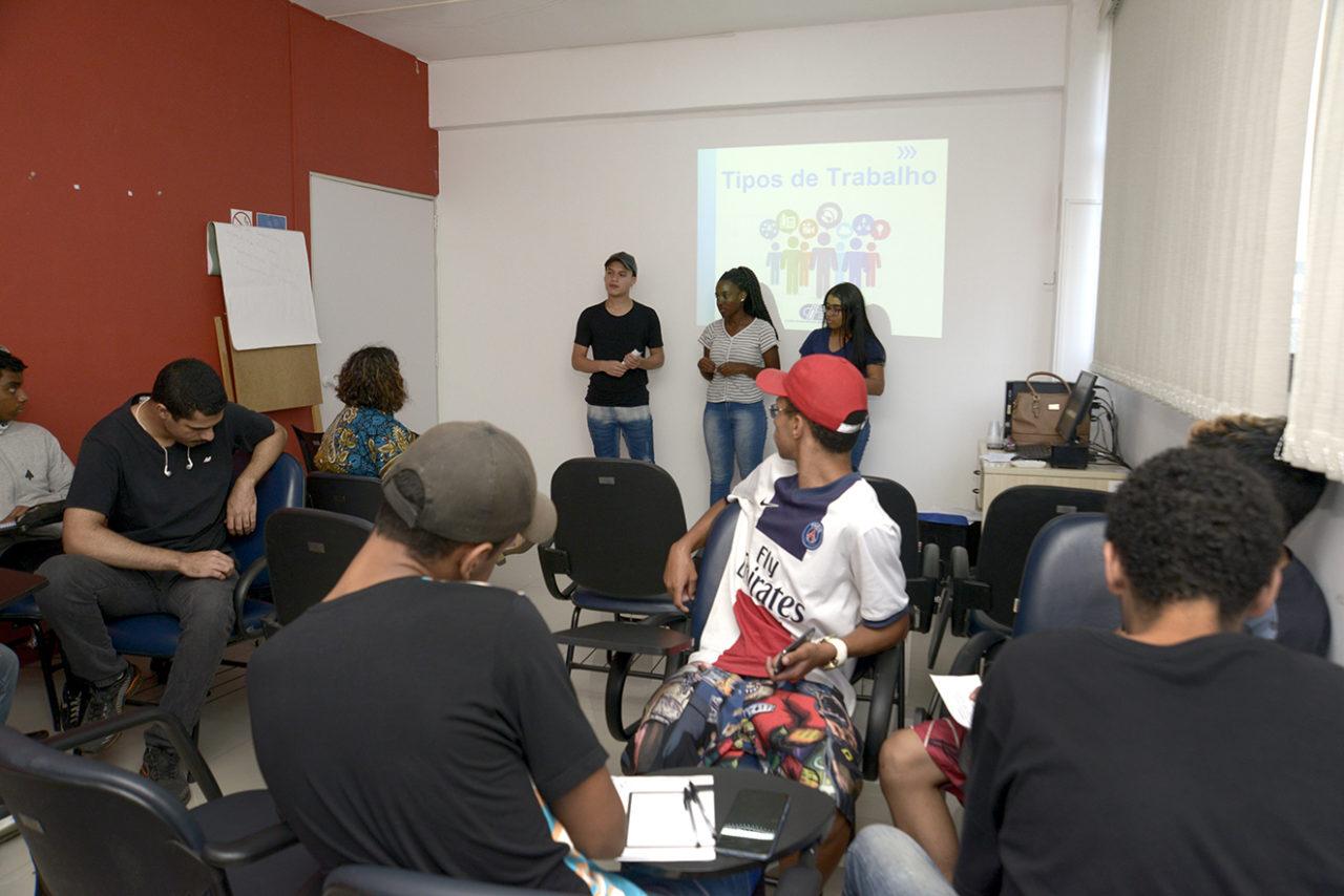 Sala de aula com pessoas sentadas e três jovens em pé falando à frente