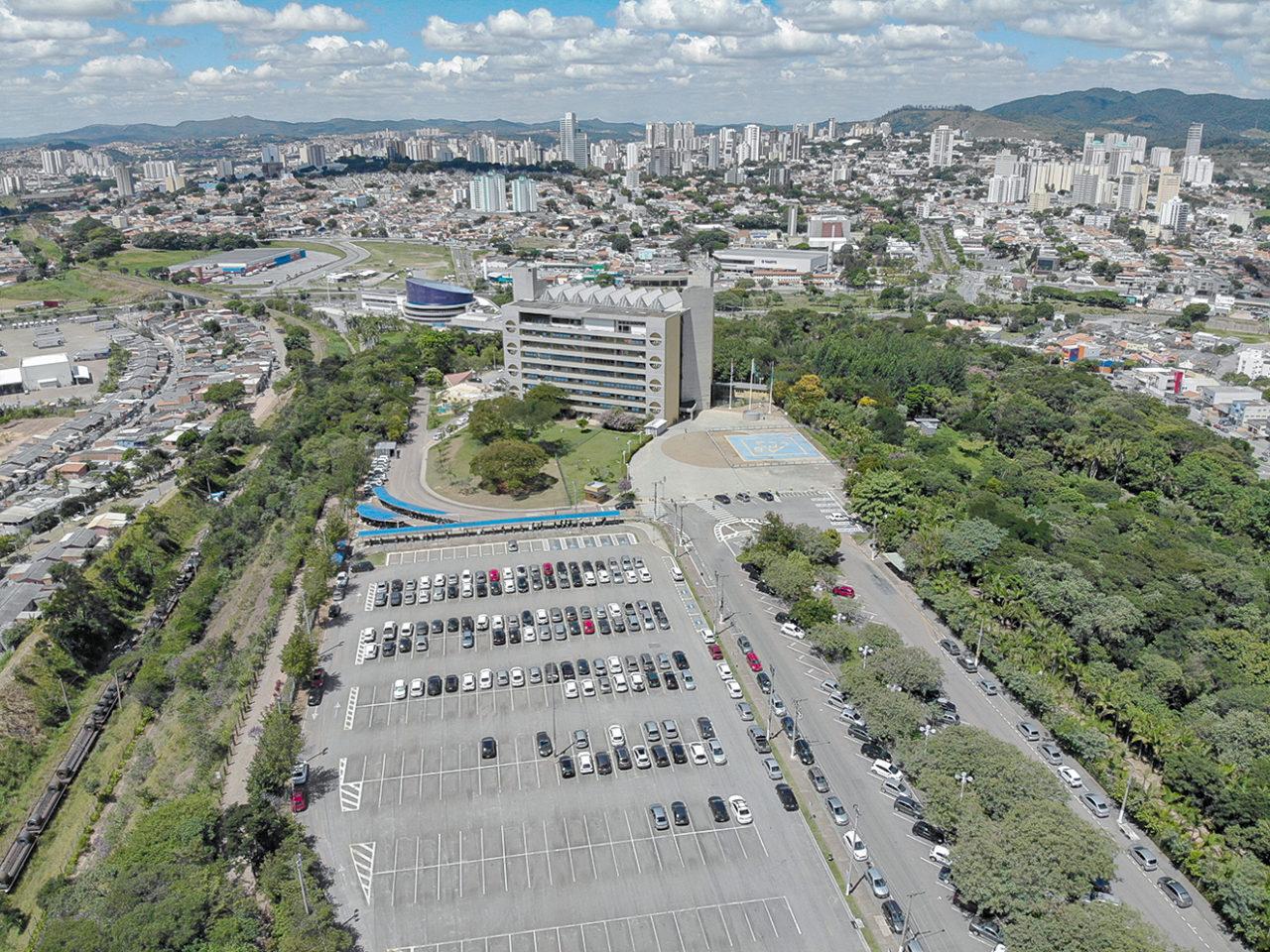 Foto Aerea de estacionamento com prédio e panorama da cidade ao fundo
