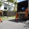 Coletores de lixo correm atrás de caminhão, um deles segurando caixas de papelão, um arremessando um saco para dentro do caminhão e outro agarrado à carreta