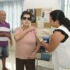Enfermeira aplica vacina em mulher idosa usando óculos de sol, com homem atrás esperando em fila