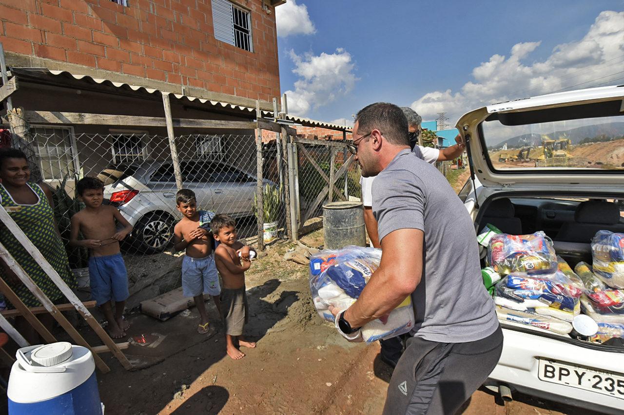Homem retirar cestas básicas de porta-malas de carro para entregar a uma mulher e três crianças em frente auma casa de tijolos com carro na garagem