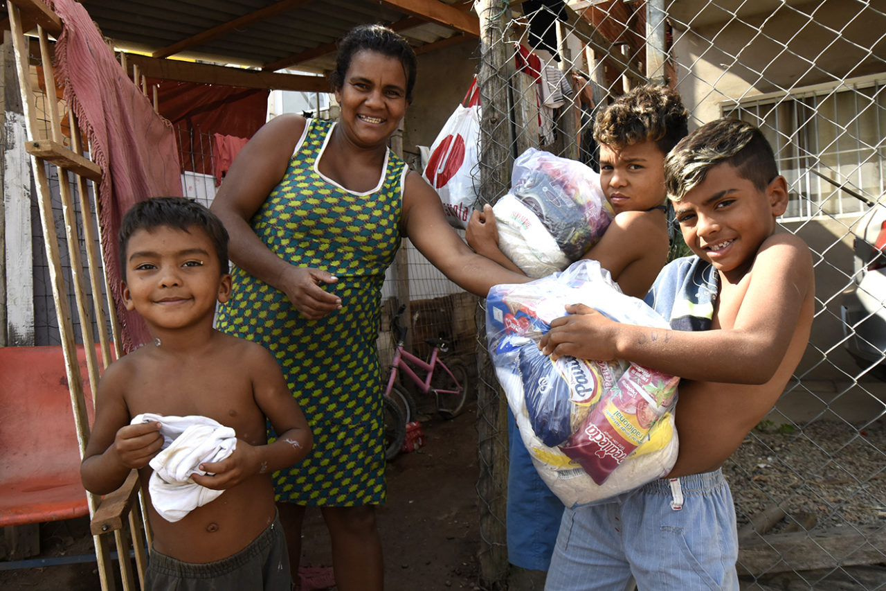 Foto posada de mulher com três meninos, segurando cestas básicas, em frente a uma casa