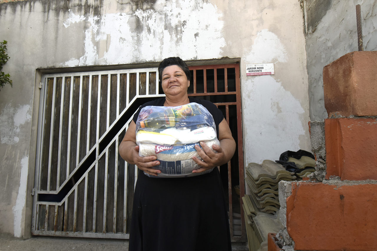Foto posada de mulher segurando cesta básica em frente à fachada de uma casa, com blocos e telhas