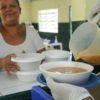 mãos com luvas brancas seguram embalagem de isopor com sopa. ao fundo, munícipe sorri com embalagens nas mãos