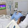 Quarto de hospital com duas pacientes e profissional da saúde uniformizada atendendo uma delas, com tela de TV ao fundo passando desenho animado