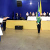 Homem com uniforme militar segurando bandeira nacional, com rapazes em posição de juramento e autoridades sobre palanque