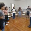 Grupo de jovens em pé, em formato de círculo, em sala de piso de madeira e com janelas ao fundo