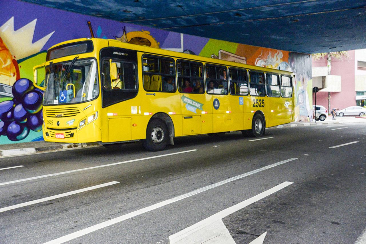ônibus transitando em avenida, sob viaduto, com parede grafitada ao fundo.