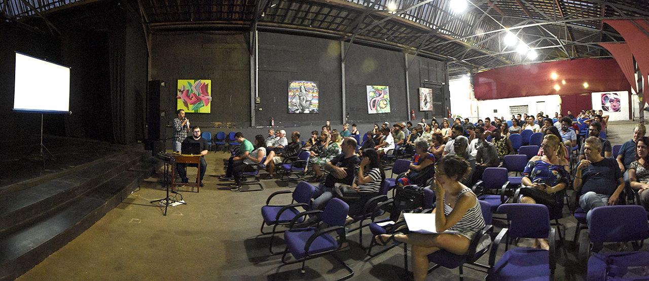 Foto panorâmica de auditório com pessoas sentadas, olhando em direção ao palco