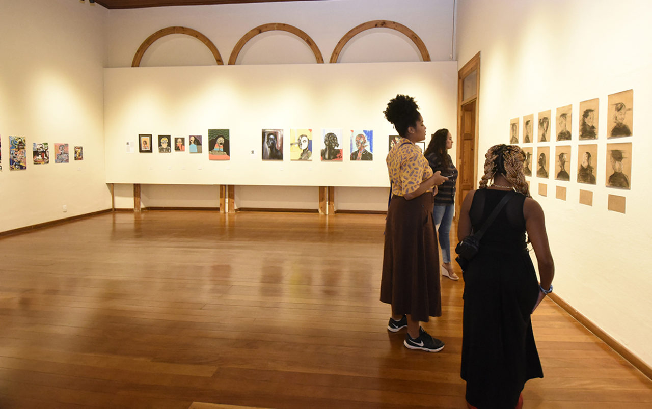 Sala de exposição de quadros, com três mulheres analisando as obras na parede da direita