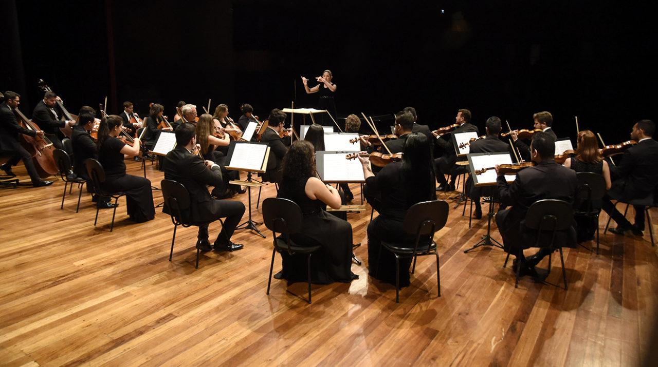 Músicos de orquestra em palco, com mulher regendo em pé e teatro em fundo escuro