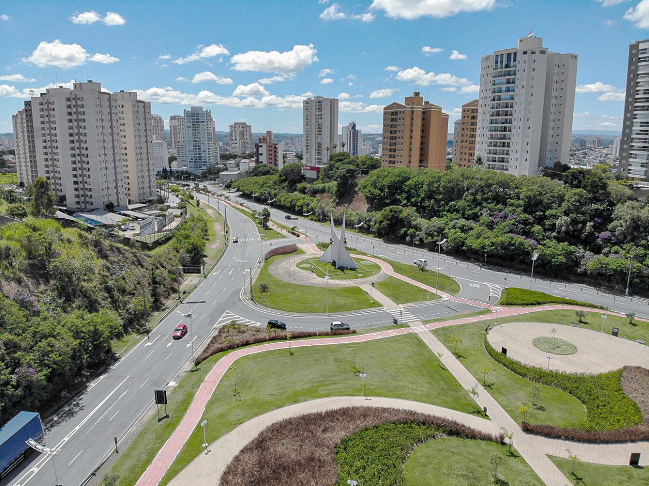Foto aérea de avenida vazia, com edifícios no entorno e jardim com desenhos paisagísticos