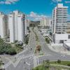 Foto aérea de avenida com pistas largas, prédios ao redor e uma praça central